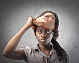 Afrikanische junge Frau, die eine Maske einer Kaukasierin abnimmt